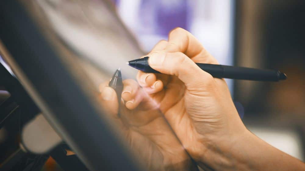 A hand grasping a stylus hovering over a workstation